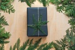 Caja de regalo de la Navidad envuelta en papel negro con la decoración del ciprés de la rama en de madera Fotografía de archivo