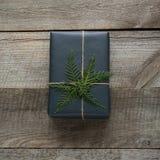 Caja de regalo de la Navidad envuelta en papel negro con los copos de nieve alrededor de ciprés de la rama en de madera Imagen de archivo libre de regalías