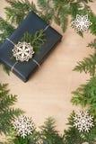 Caja de regalo de la Navidad envuelta en papel y guita negros alrededor de ciprés de la rama en superficie de madera Imágenes de archivo libres de regalías