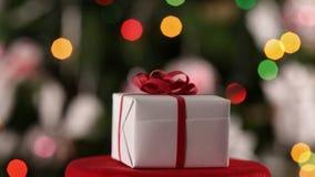 Caja de regalo de la Navidad que hace girar delante de árbol adornado de Navidad almacen de video