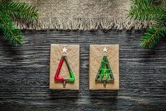 Caja de regalo de la Navidad de la rama del pino de la arpillera del vintage en el tablero de madera imagenes de archivo