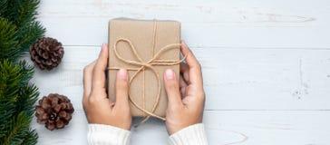 caja de regalo de la tenencia de la mujer con las ramas de árbol de la decoración y de pino de la Navidad en el fondo de madera,  fotografía de archivo