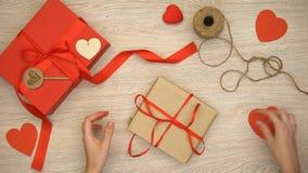 Caja de regalo de las tarjetas del día de San Valentín del arte del embalaje de la persona en el fondo de madera, preparación almacen de video