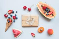 Caja de regalo linda envuelta con el papel del arte y la opinión superior de las frutas del verano Regalo del verano Foto de archivo