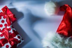 Caja de regalo llena casquillo rojo de Papá Noel en el fondo blanco fotos de archivo libres de regalías
