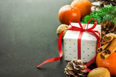 Caja de regalo de los Años Nuevos de la Navidad con el arco rojo de la cinta Ramas de árbol de abeto de las nueces de los conos d Imagen de archivo