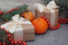 Caja de regalo de los Años Nuevos de la Navidad con el arco rojo de la cinta Ramas de árbol de abeto de las nueces de los conos d Fotografía de archivo