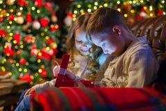 Caja de regalo mágica de la Navidad niños en el sofá en una oscuridad acogedora fotografía de archivo libre de regalías