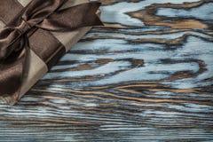 Caja de regalo marrón envuelta en fondo de madera imagen de archivo