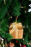 Caja de regalo minúscula del brillo del oro con la ejecución del ornamento de la Navidad del arco de la cinta del oro en el árbol Imagen de archivo libre de regalías