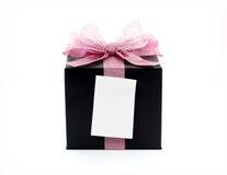 Caja de regalo negra con la cinta rosada y la nota pegajosa en blanco Fotos de archivo