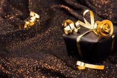 Caja de regalo negra en fondo brillante negro Imágenes de archivo libres de regalías