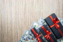 Caja de regalo negra tres con un arco con los billetes de banco de los dólares en una tabla de madera Visión superior, espacio de fotografía de archivo libre de regalías