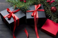 Caja de regalo negra y roja de la Navidad con salvado rojo de la cinta y del abeto Foto de archivo