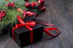 Caja de regalo negra y roja de la Navidad con salvado rojo de la cinta y del abeto Fotografía de archivo