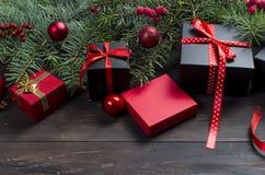 Caja de regalo negra y roja de la Navidad con salvado rojo de la cinta y del abeto Fotos de archivo libres de regalías