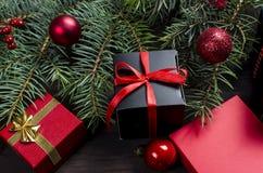 Caja de regalo negra y roja de la Navidad con salvado rojo de la cinta y del abeto Imagen de archivo