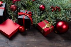 Caja de regalo negra y roja de la Navidad con salvado rojo de la cinta y del abeto Imagenes de archivo