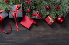 Caja de regalo negra y roja de la Navidad con salvado rojo de la cinta y del abeto Fotos de archivo
