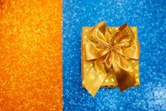 Caja de regalo de oro con un arco en un fondo chispeante del color fotografía de archivo