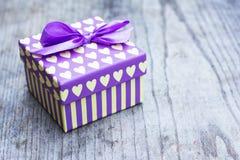 Caja de regalo púrpura con la tarjeta de felicitación amarilla de los corazones Fotos de archivo