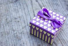 Caja de regalo púrpura con la tarjeta de felicitación amarilla de los corazones Fotografía de archivo libre de regalías