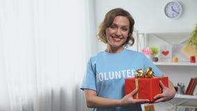 Caja de regalo que se sostiene voluntaria femenina en las manos que sonríen en cámara, donación, caridad almacen de video