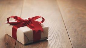 Caja de regalo rústica del papel del arte con el arco rojo de la cinta en la tabla de madera Imágenes de archivo libres de regalías