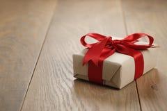 Caja de regalo rústica del papel del arte con el arco rojo de la cinta en la tabla de madera Imagen de archivo