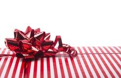 Caja de regalo rayada con un arco rojo Imagenes de archivo
