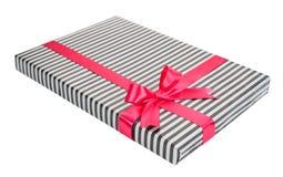 Caja de regalo rayada de moda con un arco rosado Imagen de archivo libre de regalías