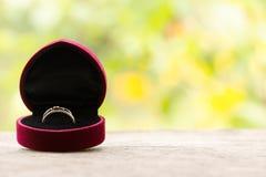 Caja de regalo roja con el anillo en el fondo del verdor y de las flores Foco selectivo, imagen entonada, efecto de la película,  Imagen de archivo