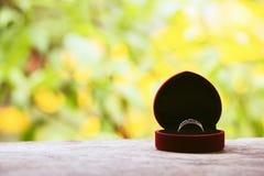 Caja de regalo roja con el anillo en el fondo del verdor y de las flores Foco selectivo, imagen entonada, efecto de la película,  Fotos de archivo