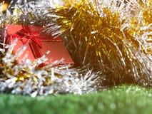Caja de regalo roja con el arco rojo de la cinta y lugar de oro de la costura en fondo de la decoración del arco iris de la plata Imagen de archivo libre de regalías