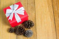 Caja de regalo roja con el cono del pino en el fondo de madera de la tabla con el espacio de la copia Foto de archivo libre de regalías