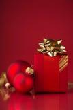 Caja de regalo roja con las cintas de oro y las chucherías de Navidad en fondo rojo Imagen de archivo libre de regalías