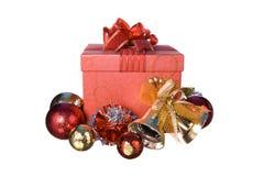 Caja de regalo roja con las decoraciones y bola del color en el fondo blanco Fotos de archivo