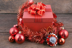 Caja de regalo roja con las decoraciones y bola del color en el fondo de madera Imagen de archivo