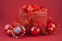 Caja de regalo roja con las decoraciones y bola del color en fondo rojo Fotos de archivo libres de regalías