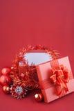Caja de regalo roja con las decoraciones y bola del color en fondo rojo Foto de archivo