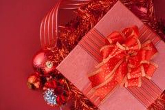 Caja de regalo roja con las decoraciones y bola del color en fondo rojo Fotografía de archivo libre de regalías