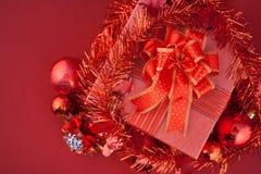 Caja de regalo roja con las decoraciones y bola del color en fondo rojo Imagen de archivo libre de regalías