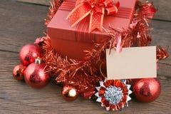 Caja de regalo roja con las decoraciones y bola del color en la madera Imágenes de archivo libres de regalías