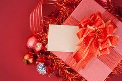 Caja de regalo roja con las decoraciones y bola del color en la madera Foto de archivo libre de regalías