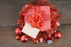 Caja de regalo roja con las decoraciones y bola del color en la madera Foto de archivo