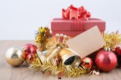 Caja de regalo roja con las decoraciones y bola del color en la madera Imagen de archivo