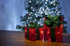 caja de regalo roja con las luces y el fondo oscuro fotos de archivo