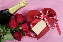 Caja de regalo roja de la forma del corazón del día de tarjetas del día de San Valentín con la botella de champán y de rosas roja Imagen de archivo libre de regalías