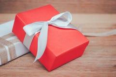 Caja de regalo roja en el estilo de madera del vintage del fondo de la tabla con el espacio de la copia Fotografía de archivo