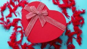 Caja de regalo roja, en forma de corazón colocada en fondo azul entre plumas rojas